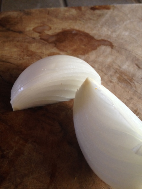 The onion, lying on its side for slicing.
